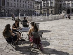 Three friends enjoying the sun in the courtyard of Somerset House London.