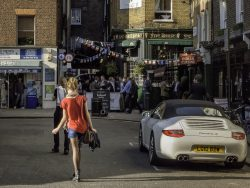 Girl in red top walking in Shepherd Market Mayfair London UK, on an evening in Spring